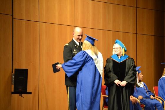 Lauren receiving her diploma from Dr Brezel and LTC Strange