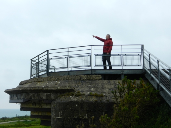Standing on top of a German bunker, Tim points out the direction the Allies came from