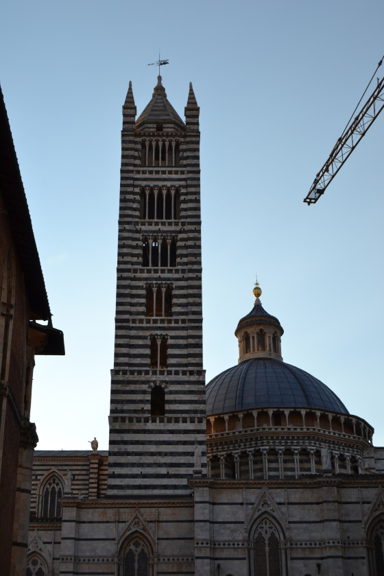The stark black and white marble of Siena Cathedral at dusk