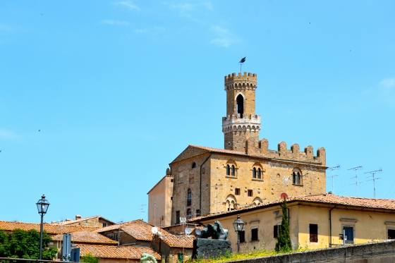 Tower stands tall against the bright Tuscan sky in Volterra