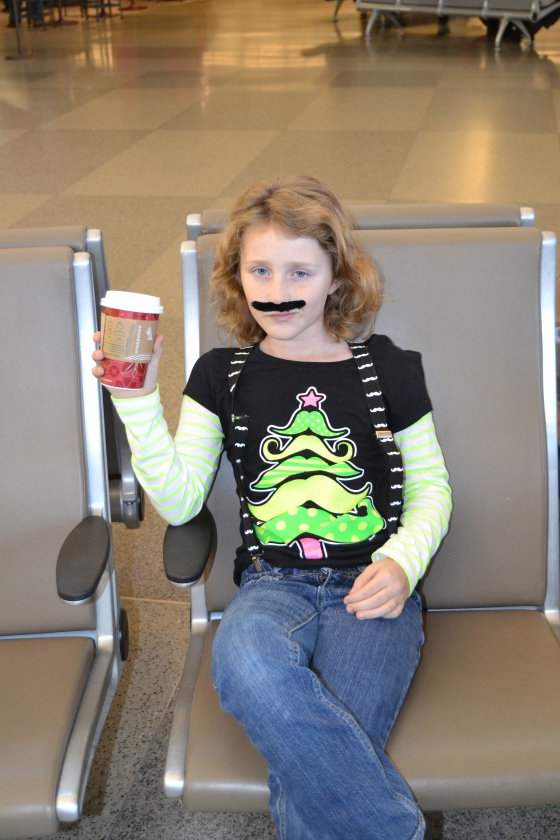 Lilly casually drinks her hot chocolate even though the stache gets in the way of the whipped cream