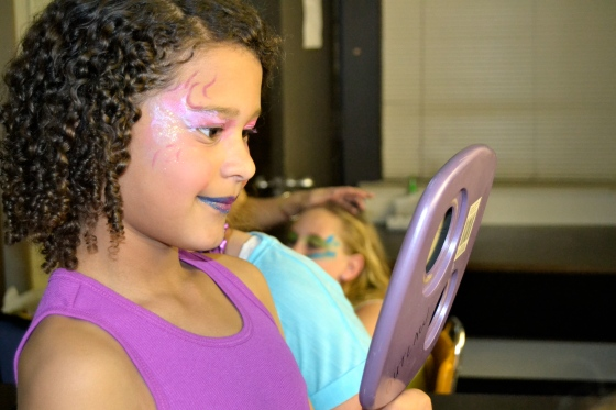 A team of moms devoted their time to doing stage makeup for the cast. Here, a mermaid admires her new look