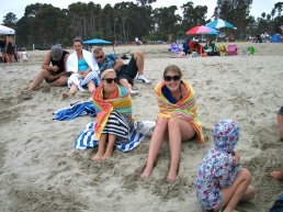Danah and Lindsey snuggle under blankets on a cool July day at Doheny Beach