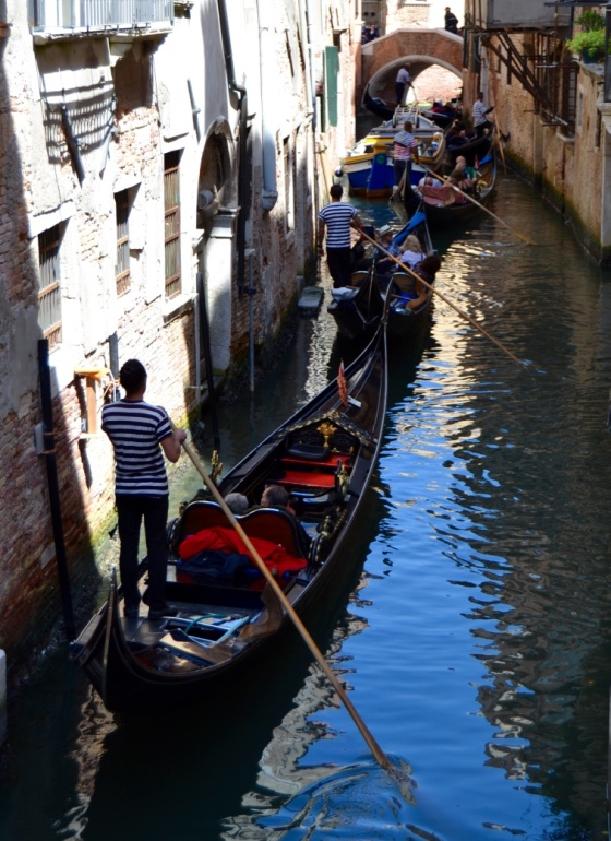A line of gondoliers in a Venice canal